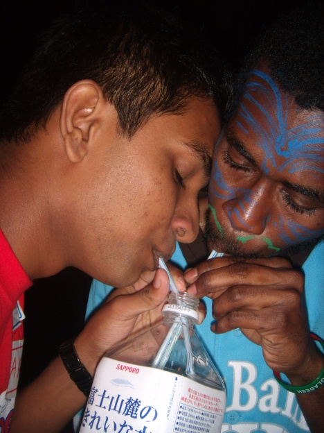 2 boys sharing a bottle of water